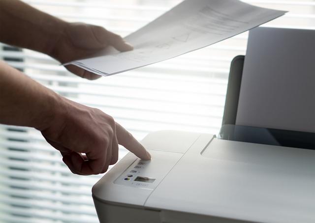 prst mačkající tlačítko na tiskárně