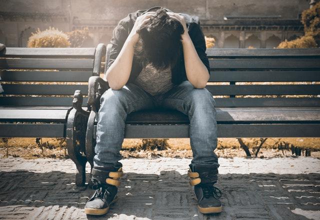 muž na lavičce se drží za hlavu