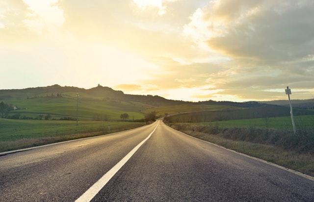 silnice, kolem je tráva, pole a louky