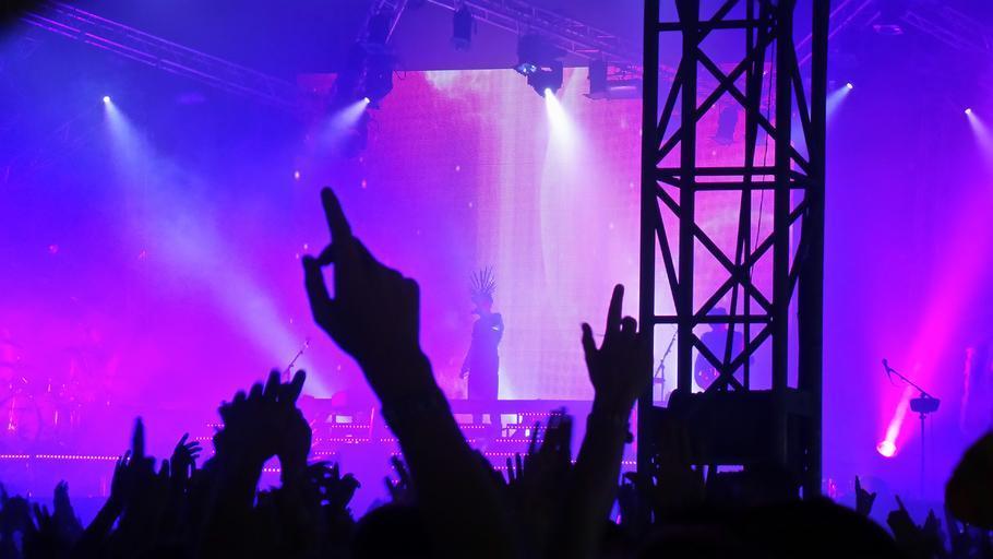 velká akce, koncert venku, sloup, ruce nahoře, pódium, na kterém je zpěvák, fialová barva všude