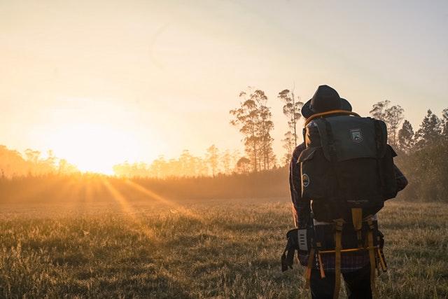 muž na cestách s batohem na zádech