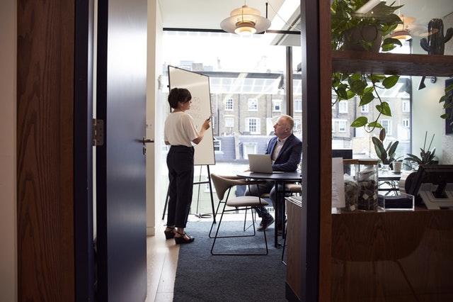 kancelář, žena stojí u tabule a ukazuje muž